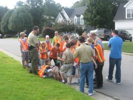 A group of people, some wearing orange safety vests, are huddled together on the street.