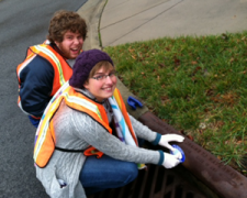Young man and woman in orange safety vests marking a storm drain