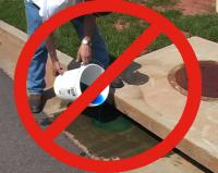 "Person dumping a blue chemical down a storm drain with a large red circle and diagonal ""Do Not&#3"