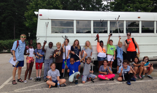 Kids posing and holding their cleaning tools outside of a white bus.